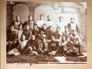 "PREP SCHOOL OR COLLEGE FOOTBALL TEAM ALBUMEN PHOTOGRAPH, CIRCA 1894, SHOWING TWENTY YOUNG MEN IN MISMATCHED UNIFORMS SEATED IN FRONT OF VINED PILLARS. ONE HOLDS A LARGE FOOTBALL WITH '96 PAINTED ON IT; A FEW HAVE LETTERS ""S"" AND ""W"" ON OPPOSITE SHOULDERS OF THEIR VESTS, ONE WITH THE LETTER ""M"" ON HIS JERSEY AND ONE WITH ""SV""; A FEW WITH THE YEARS '94 OR '96 ON THEIR JERSEYS, TWO WEARING MILITARY STYLE UNIFORMS. ONE APPEARS ESPECIALLY YOUNG AND SITS IN THE FRONT ROW WEARING A SUIT. Football."